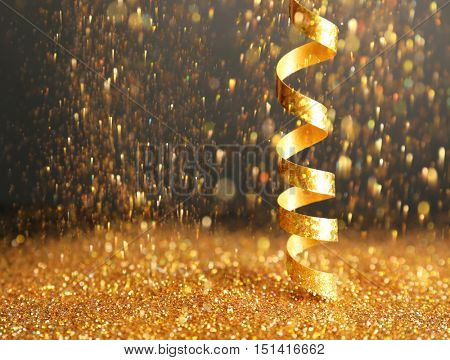 Shiny golden streamer and glitter on dark background
