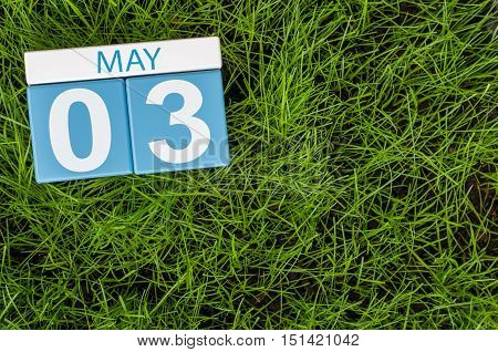 May 3rd. Day 3 of month, calendar on football green grass background. Spring time, empty space for text.