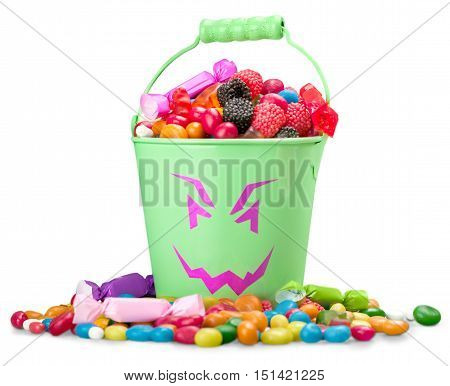 Jack-o-lantern candy pail with a pile of colorful Halloween candy