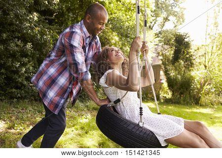 Man Pushing Woman On Tire Swing In Garden