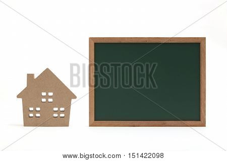 Miniature house and miniature blackboard on white background.