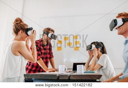 Team of developers working with virtual reality glasses during a business meeting. Young business colleagues brainstorming using VR goggles.