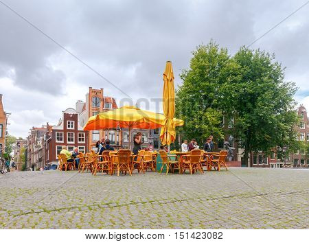 Amsterdam, The Netherlands - August 29, 2016: Traditional Dutch street cafe on the bridge Singel. These cafes are very popular among tourists and residents.