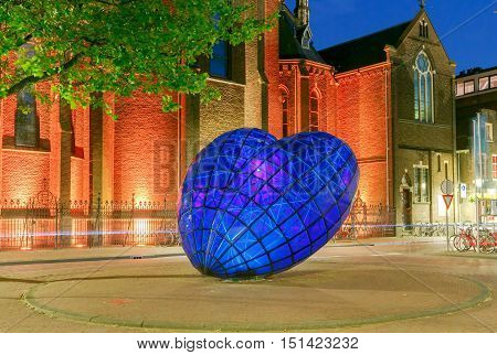 Delft, The Netherlands - August 30, 2016: Glowing Blue Heart sculpture in the center of the city at night. One of the attractions of Delft.