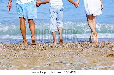Couple holding hands walking romantic on beach on vacation travel holidays leaving footprints in the sand. Closeup of feet and golden sand for copy space. Young couple wearing white shorts