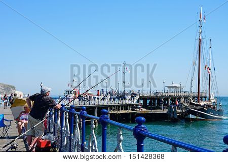 SWANAGE, UNITED KINGDOM - JULY 19, 2016 - Tourists of the Victorian pier enjoying the Summer sunshine Swanage Dorset England UK Western Europe, July 19, 2016.