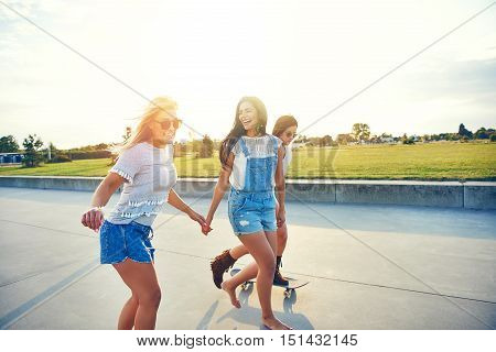 Three young female friends skateboarding at sunrise along a seaside promenade overlooking a green field as they enjoy their summer vacation