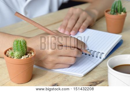 female hands with pencil writing on notebook