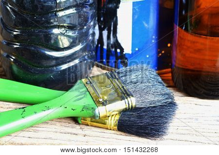 paintbrush and paint can on wooden table