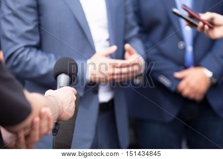 Journalists making interview with businessperson or spokesperson. Press conference.