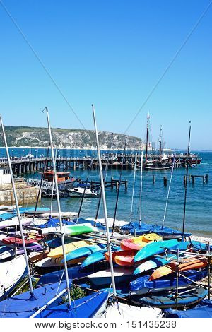 SWANAGE, UNITED KINGDOM - JULY 19, 2016 - Dinghies moored on the beach with the pier and coastline to the rear Swanage Dorset England UK Western Europe, July 19, 2016.