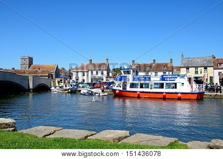 WAREHAM, UNITED KINGDOM - JULY 19, 2016 - Boats moored on the river with views towards the bridge and town Wareham Dorset England UK Western Europe, July 19, 2016.