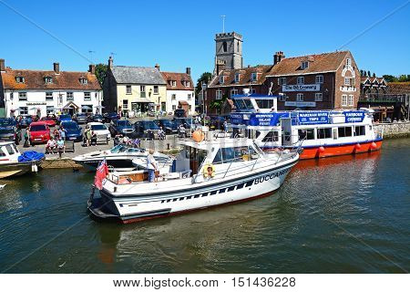 WAREHAM, UNITED KINGDOM - JULY 19, 2016 - Boats on the river with views towards The Old Granary and Lady St Mary church Wareham Dorset England UK Western Europe, July 19, 2016.