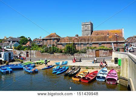 WAREHAM, UNITED KINGDOM - JULY 19, 2016 - Boats and canoes moored on the banks of the river Wareham Dorset England UK Western Europe, July 19, 2016.