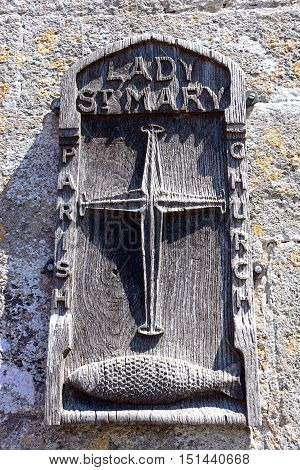WAREHAM, UNITED KINGDOM - JULY 19, 2016 - Wooden Lady St Mary parish church sign on the church wall Wareham Dorset England UK Western Europe, July 19, 2016.