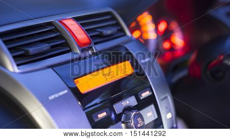 Transportation vehicle and car auto audio concept - Car audio and radio stereo system on car panel in evening ligth