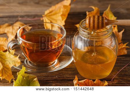 Rose Hip Tea In Transparent Cup And Teapot With Honey And Autumn Leaves. Hot Autumn Drink