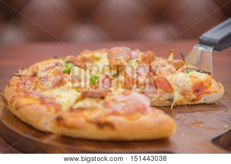 Selective Focus On Meat Deluxe Pizza Slice On Pizza Scoop