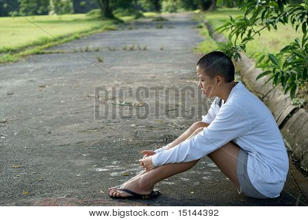 Sad bald asian woman seated on ground