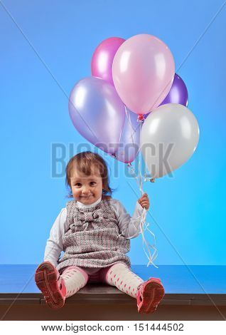 Little Girl With Balloons On A Blue Background
