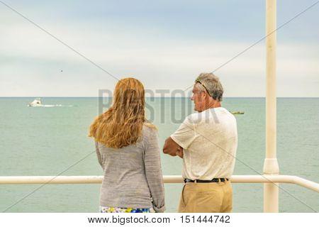 SALINAS, ECUADOR, OCTOBER - 2015 - Aged couple watching the ocean at viewpoint in Salinas beach Ecuador