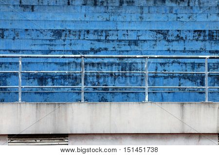 Blue concrete bleachers steps and railing in horizontal 3:2 format.