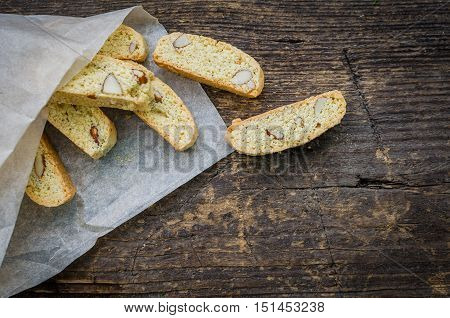 Italian cantuccini cookies. Traditional italian almond cookies biscotti overhead view on old wooden background. Homemade Almond cookies with space for text on wooden table. Top view. Copy space.