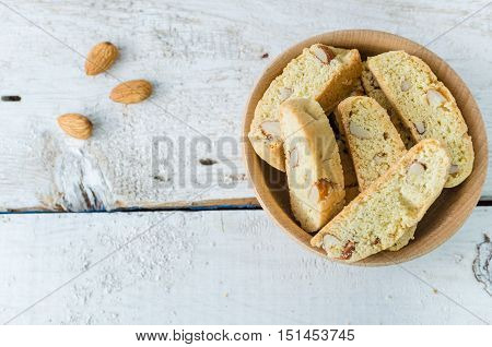 Italian cantuccini cookies in a bowl with almonds. Traditional italian almond cookies biscotti on white wooden background. Homemade cookies with space for text on wooden table. Top view. Copy space.