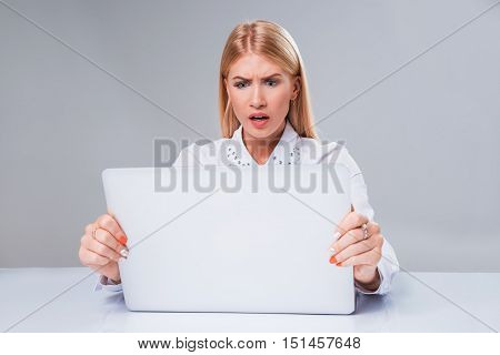 Young businesswoman working at laptop computer. surprised and incredulous looks