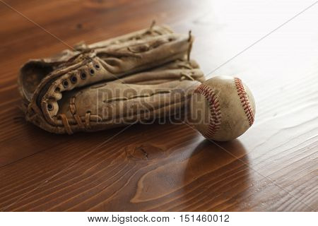 A selective focus view of a vintage baseball and mitt on pine wood background