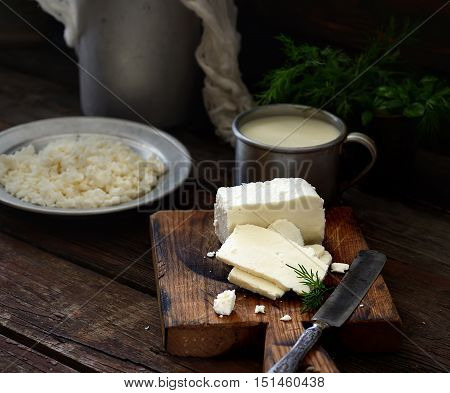 cottage cheese on a cutting board, cup of milk and water-can. rustic style