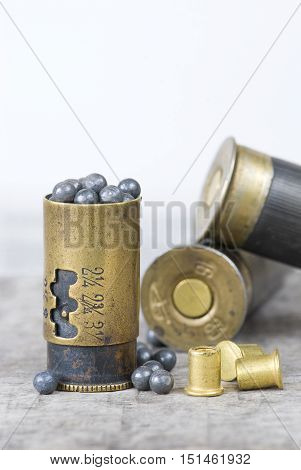 jigger of lead shot and two hunting cartridges on an old wooden board