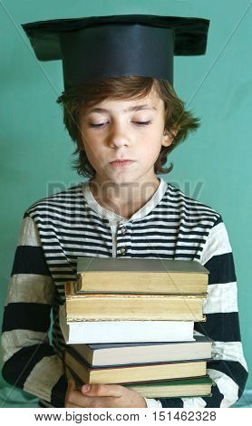 preteen handsome boy in graduation cap with book pile close up photo