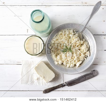 Plate of homemade cottage cheese, served with vintage aluminum pan , cheese, milk and knife on a white wooden background. rustic style