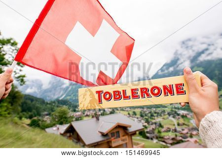 Grindelwald, Switzerland - June 26, 2016 Female hand holds Toblerone chocolate with swiss flag on the mountains background in Switzerland. Toblerone is a famous Swiss chocolate bar brand