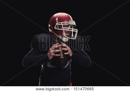 Soccer player on a dark background in vintage style. The classic American game. college Students. He makes the ball roll