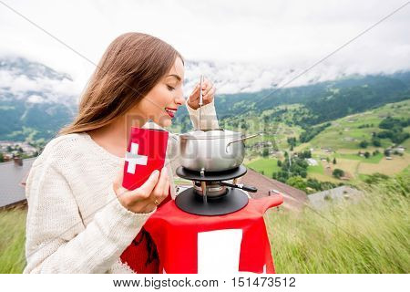 Young woman eating fondue a traditional swiss meal during a trip in the mountains in Switzerland