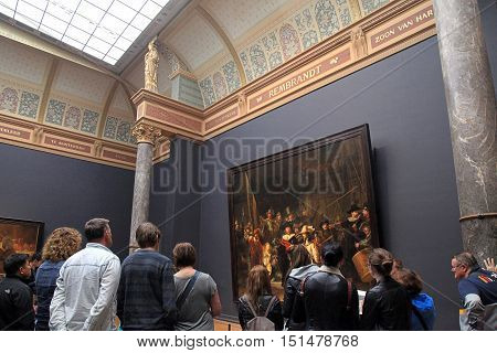 AMSTERDAM, THE NETHERLANDS - MAY 4, 2016: Visitors looking at the famous The Night Watch by Rembrandt at the Rijksmuseum in Amsterdam, Netherlands.