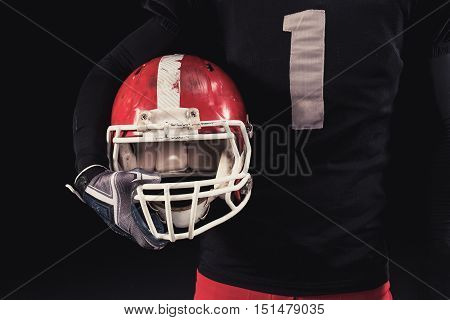 Soccer player on a dark background in vintage style. The classic American game. college Students. close-up helmet