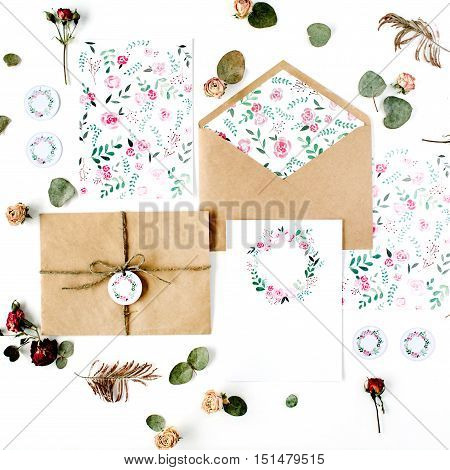 Flat lay workspace. Wedding invitation cards craft envelopes pink and red roses and green leaves on white background. Overhead view top view
