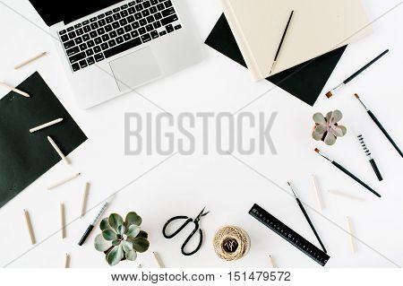 Flat lay top view office table desk. Workspace with laptop scissors pencils succulent and diary on white background.
