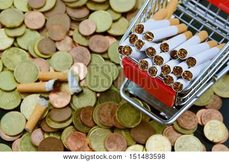Buying cigarettes lose money and health . (soft focus,lens blur) cigarette in the shopping cart , money
