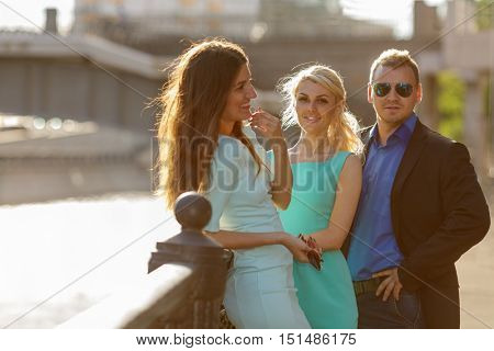 Group portrait of man and two women on sun-drenched waterfront