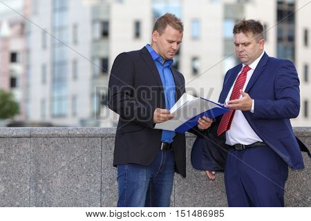 Two mature well dressed businessman outside discussing contract
