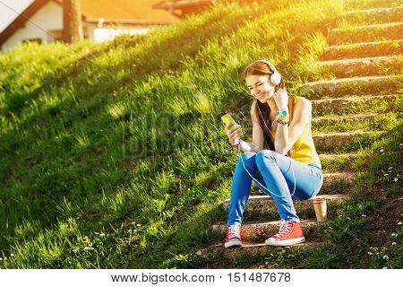 Cheerful millennial blonde teenage girl, sitting on stairs outdoors, with smart phone and headphones. Young female student in park smiling and relaxing. Natural light, medium retouch, vibrant colors.