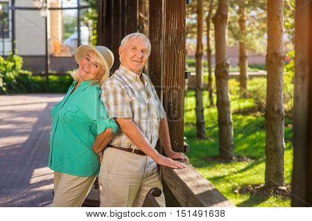 Elderly man and woman smiling. Senior couple near fence. Love and trust are priceless. We share happiness for two.