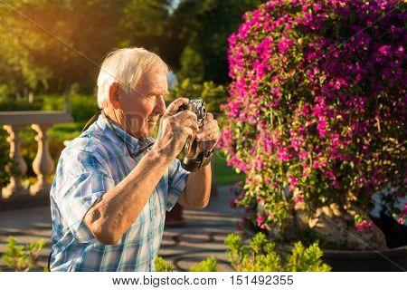 Senior male holding camera. Elderly man outdoor. Photographs of nature in summer. Wonderful life around us.