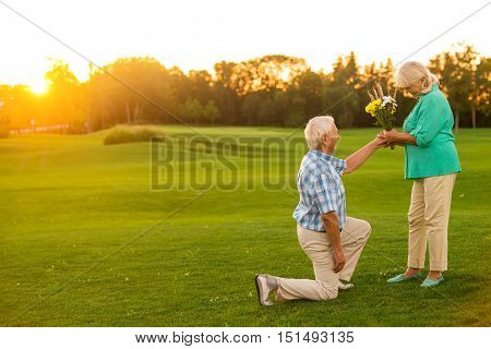 Man with bouquet kneeling. Couple of seniors on grass. Accept this small gift. Manners of true gentleman.