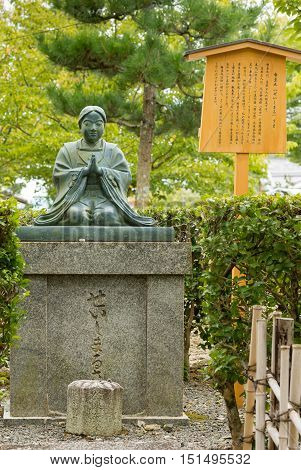 Kyoto Japan - September 15 2016: Kneeling Quan Yin statue at Kurodani Buddhist Temple. Green statue stands on top of stone pedestal. Background green trees and yellow sign.
