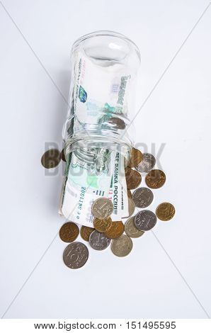 Glass jar with bills and coins on white background